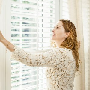 Woman opening curtains to allow natural light to enter her home