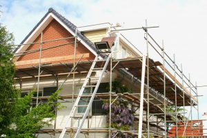 Exterior renovation of a modern house and construction equipment