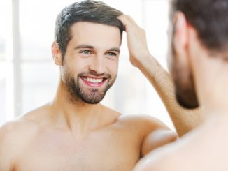 Man touching his hair while looking at the mirror