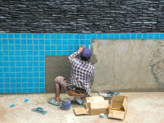 Man fixing the tiling of the pool