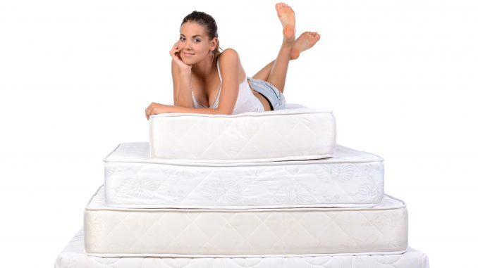 a woman lying on a stack of mattresses