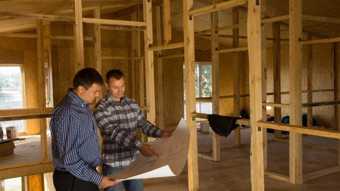 Two builders standing with an open blueprint discussing the interior of a custom home
