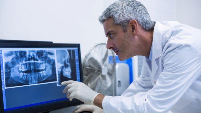 Dentist examining xray photo