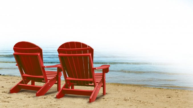 red wooden beach chairs placed by the ocean shore