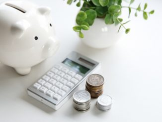 a piggy bank and an electronic calculator with coins on the side