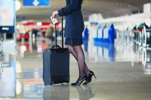 a flight attendant holding her luggage in the airport