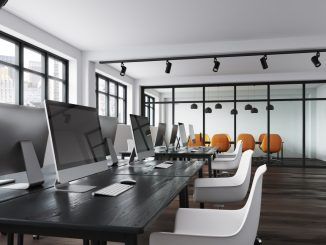 minimalist office workspace with white chairs and silver desktops