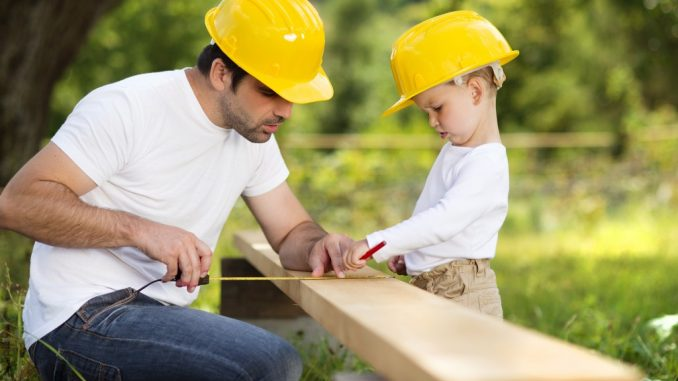 Little son helping his father with building house