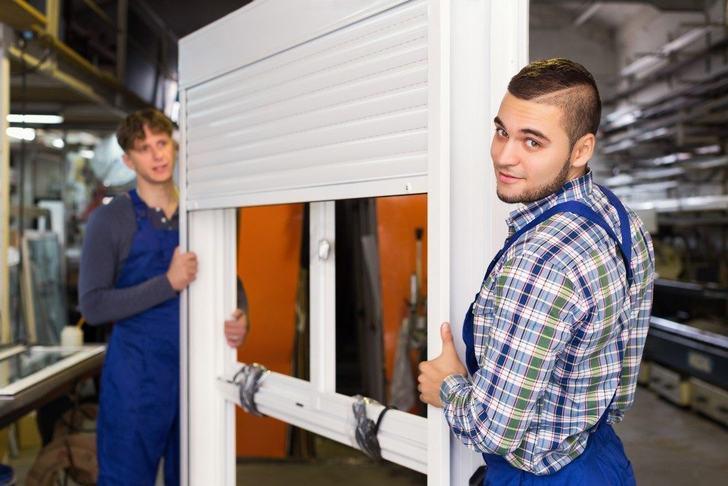 Two young careful workmen inspecting windows with shutter