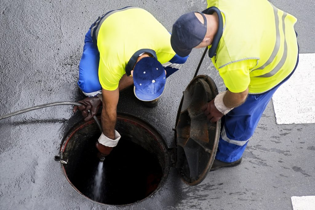 Workers cleaning the sewer