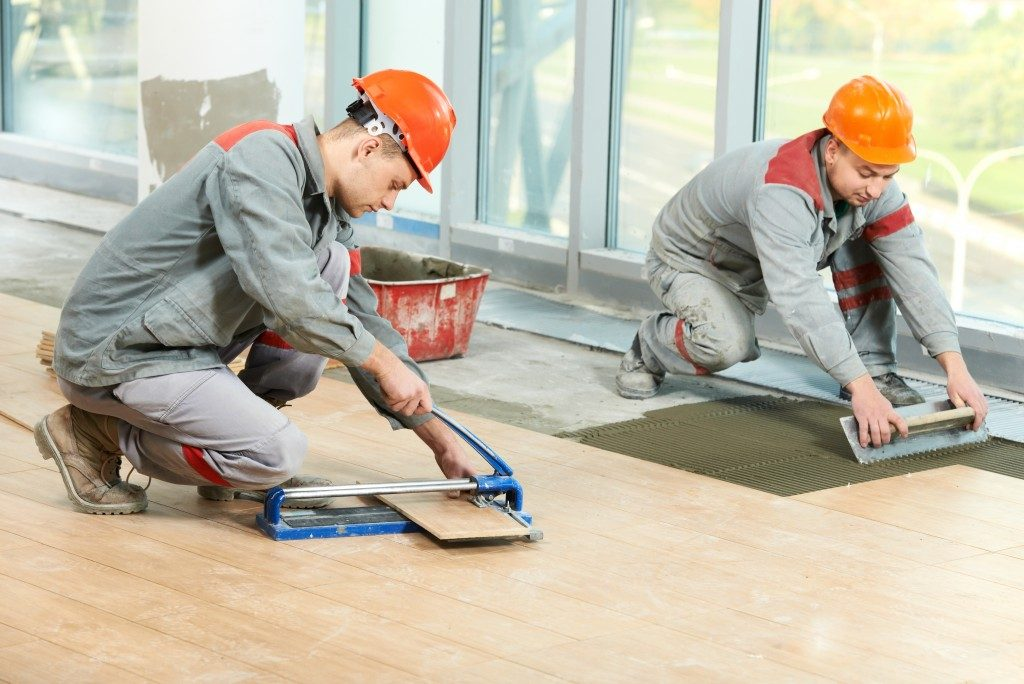 Men cutting and installing tile