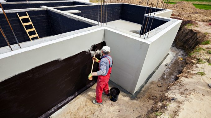 Man waterproofing foundation of building
