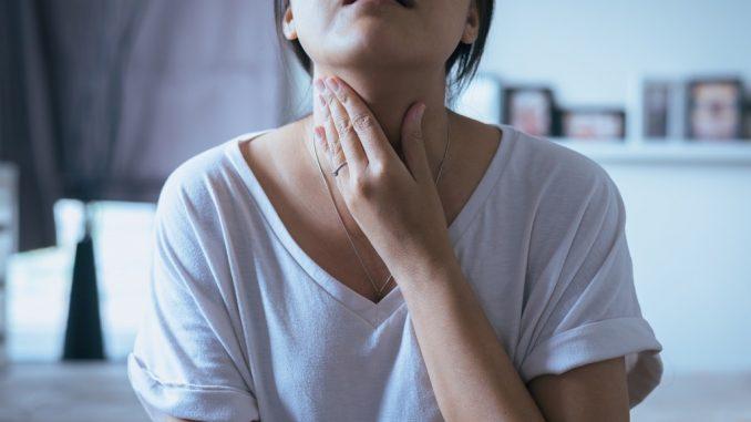woman clutching her throat