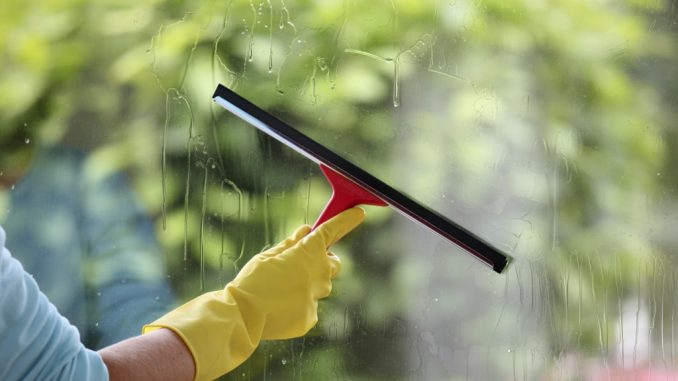 person cleaning window with squeegee