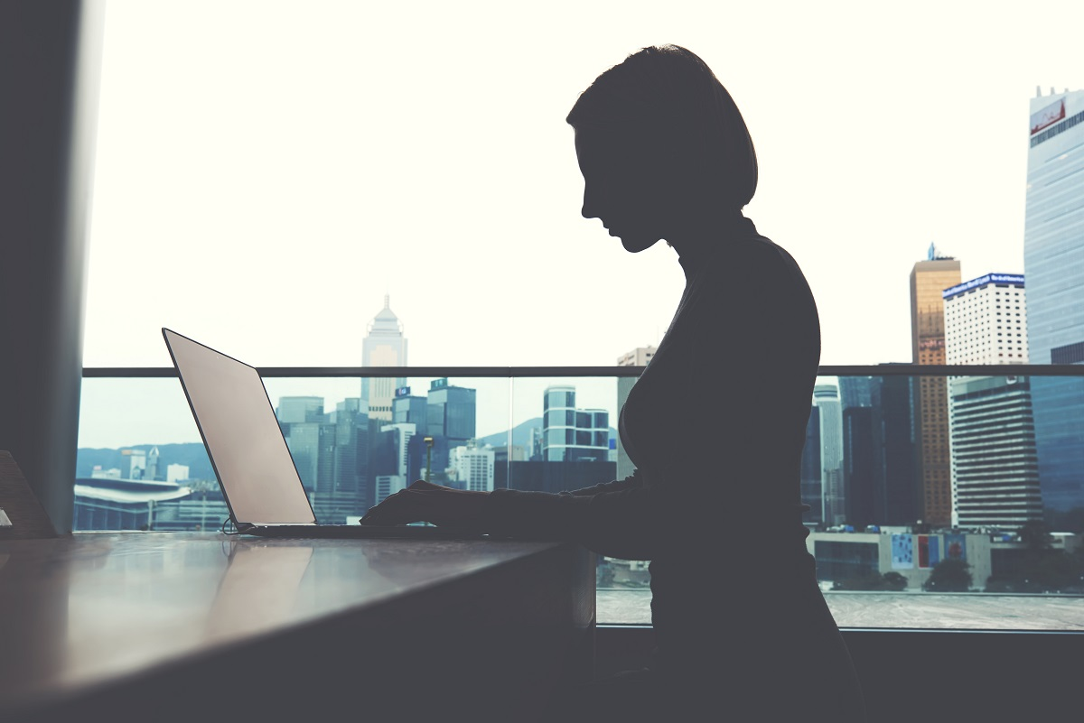 Silhouette of a woman using her laptop