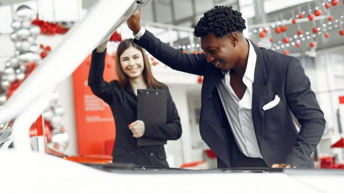 man inspecting the hood of a car