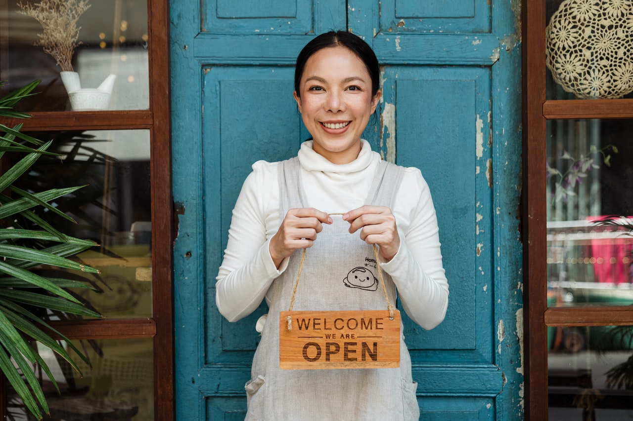 business owner holding a open signage