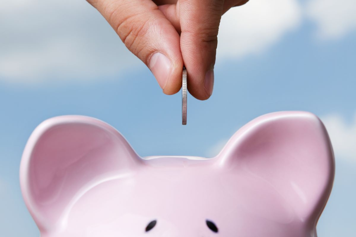 putting coin in piggy bank saving money
