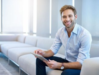 man smiling while holding a tablet